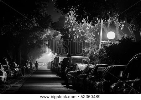 City night with cars parked at small lane and one man walk alone, shot at Taipei, Taiwan, Asia.
