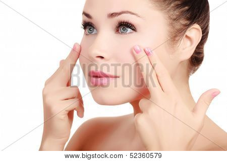 Woman massaging her face with her fingers, white background