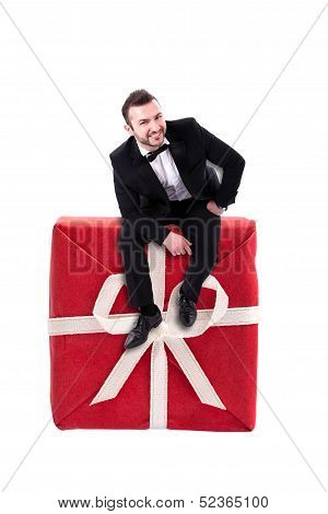 Smart Looking Man Sitting On A Hude Red Gift Box
