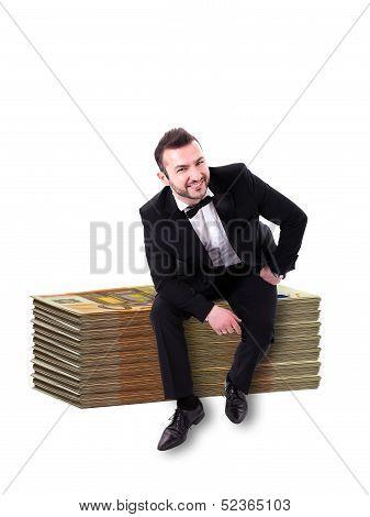 Man Smiling Sitting On Huge Stack Money