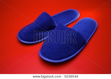 Blue Slippers On Red Background