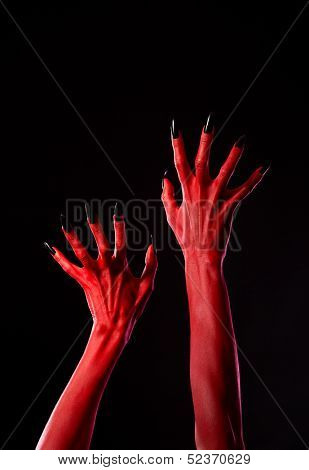 Spooky red demonic hands with black nails, Halloween theme, studio shot