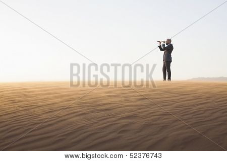 Young businessman looking through telescope in the middle of desert