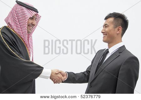 Smiling businessman and young man in traditional Arab clothing shaking hands