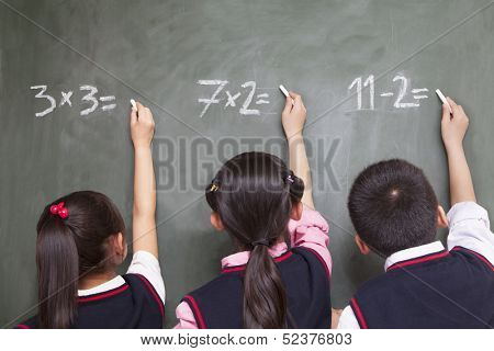 Three children doing math equations on blackboard