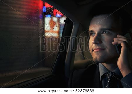 Businessman on the phone in backseat of car looking into window