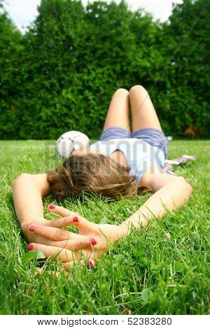 Teenager relax in a grass after a soccer game