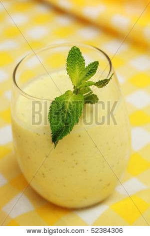 Mango or banana smoothie with fresh mint on yellow background