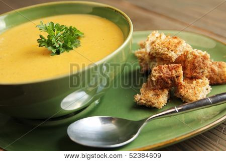 Vegetables soup with bread and spoon on a wooden table