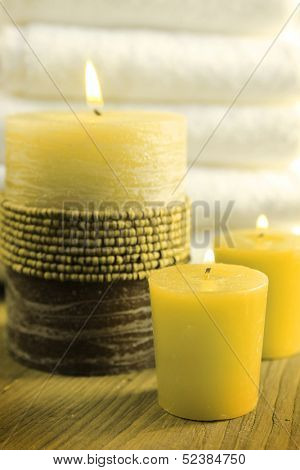 Green candles with white towels in a background