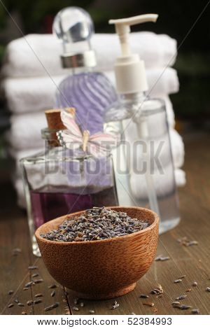 Lavender items, oil, cream, dried lavender and towels in background