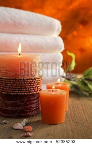 Orange candles with white towels in a background