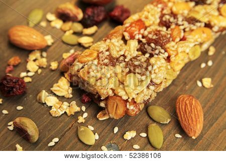 Organic granola bar with nuts and dry fruits on a wooden table