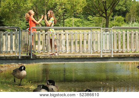 Teenager girl playing with hands on a bridge by a nice summer day