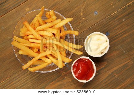 French fries with a choice of ketchup and mayonnaise on a wooden table