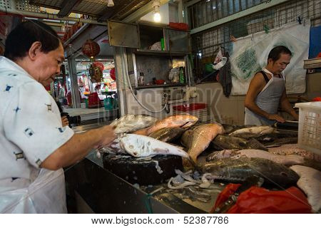 SINGAPORE - SEPTEMBER 19: Two fishmongers sell various fresh fishes in a stall on September 19, 2013 in Toa Payoh Market, Singapore. The traditional Asian wet market still exist in this modern city.