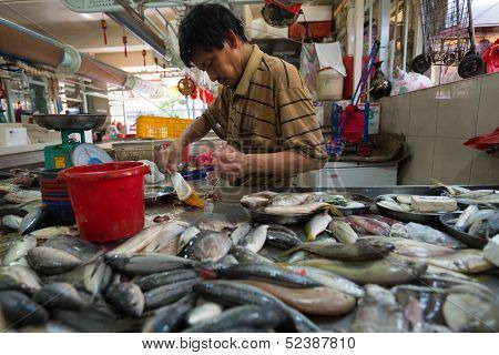 SINGAPORE - SEPTEMBER 19: A fishmonger sells various fresh fishes in a stall on September 19, 2013 in Toa Payoh Market, Singapore. The traditional Asian wet market still exist in this modern city.