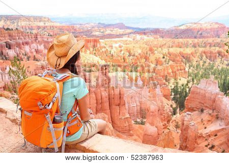 Hiker woman in Bryce Canyon hiking looking and enjoying view during her hike wearing hikers backpack. Bryce Canyon National Park landscape, Utah, United States.