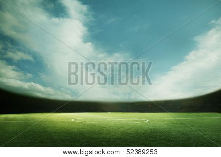 Digital composition of soccer field and blue sky