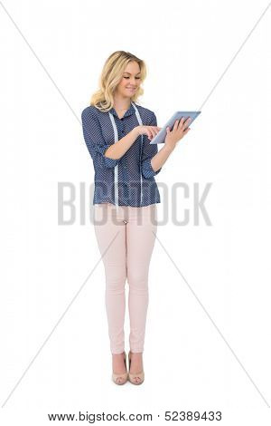 Cheerful pretty fashion designer using tablet on white background