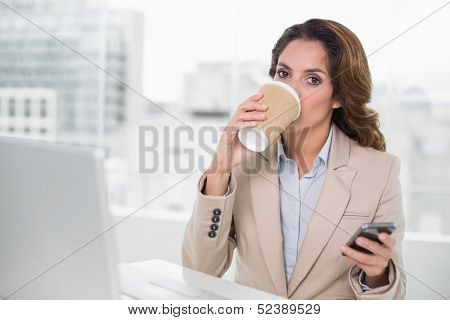 Attractive businesswoman drinking from disposable cup at her desk in bright office