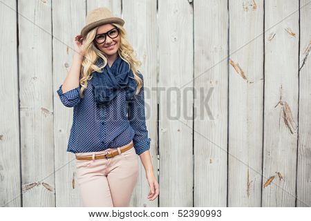 Smiling trendy model posing on wooden background