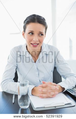 Skeptical stylish brunette businesswoman joining her hands and looking away in bright office