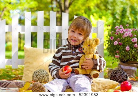 Little Boy With An Apple And A Teddy Bear Sitting In The Autumn