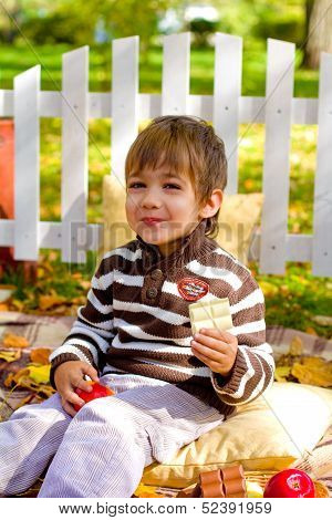 Happy Little Boy Eating Chocolate In The Autumn Forest