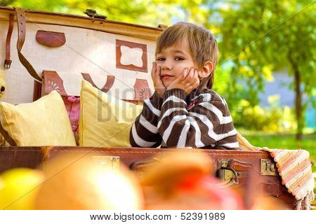 Little Boy Sitting In An Old Suitcase