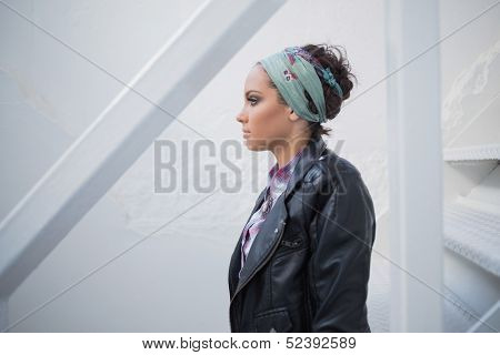 Side view of attractive woman with hairband sitting on stairs