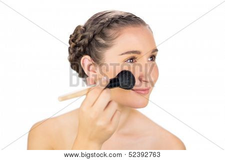 Relaxed gorgeous model on white background applying blusher