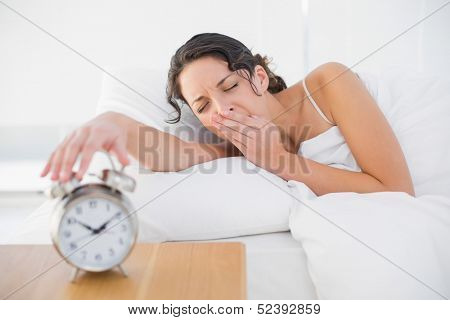 Awake casual brunette in white pajamas turning off her alarm clock in bright bedroom
