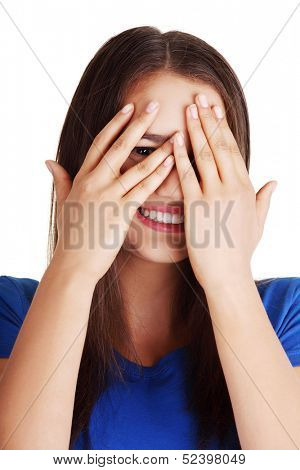 Shy teenage girl peeking through covered face , isolated on white.