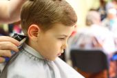 stock photo of hair cutting  - Little serious Boy cut in hairdresser - JPG
