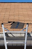 picture of wind blown  - A ladder set up to repair damaged roof shingles - JPG