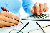 stock photo of economics  - Hands of accountant with calculator and pen - JPG