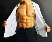stock photo of nipple  - Muscular and tanned male torso isolated on black background
