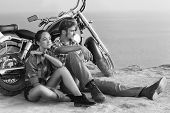Black and white photo. Biker man and girl