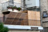 picture of sukkoth  - A partially assembled sukkah on a balcony