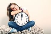 Young girl sit and holding a clock showing noon or midnight