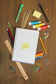 School material, pencil, rule, brushes, paper clips on a wooden table with a note book with a postit