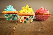 Three different colors cupcakes on a wooden table, blue, yellow and pink.