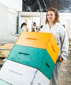 Female beekeeper pushing trolley of stacked honeycomb crates in beekeeping factory