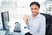 Pleased young dark haired businesswoman holding a cup of coffee in bright office