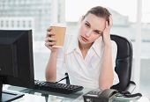 Stressed businesswoman holding disposable cup looking at camera in her office