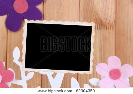 Holder in form of tree with instant photo card on wooden background