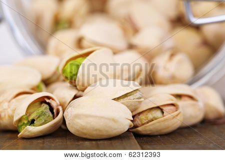 Pistachio nuts in glass jar on table close up