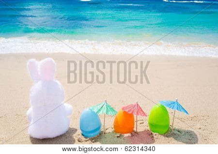 Easter Bunny And Color Eggs On The Beach