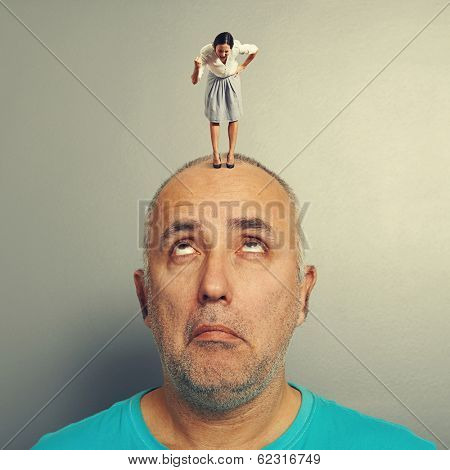surprised man with small angry businesswoman on his head